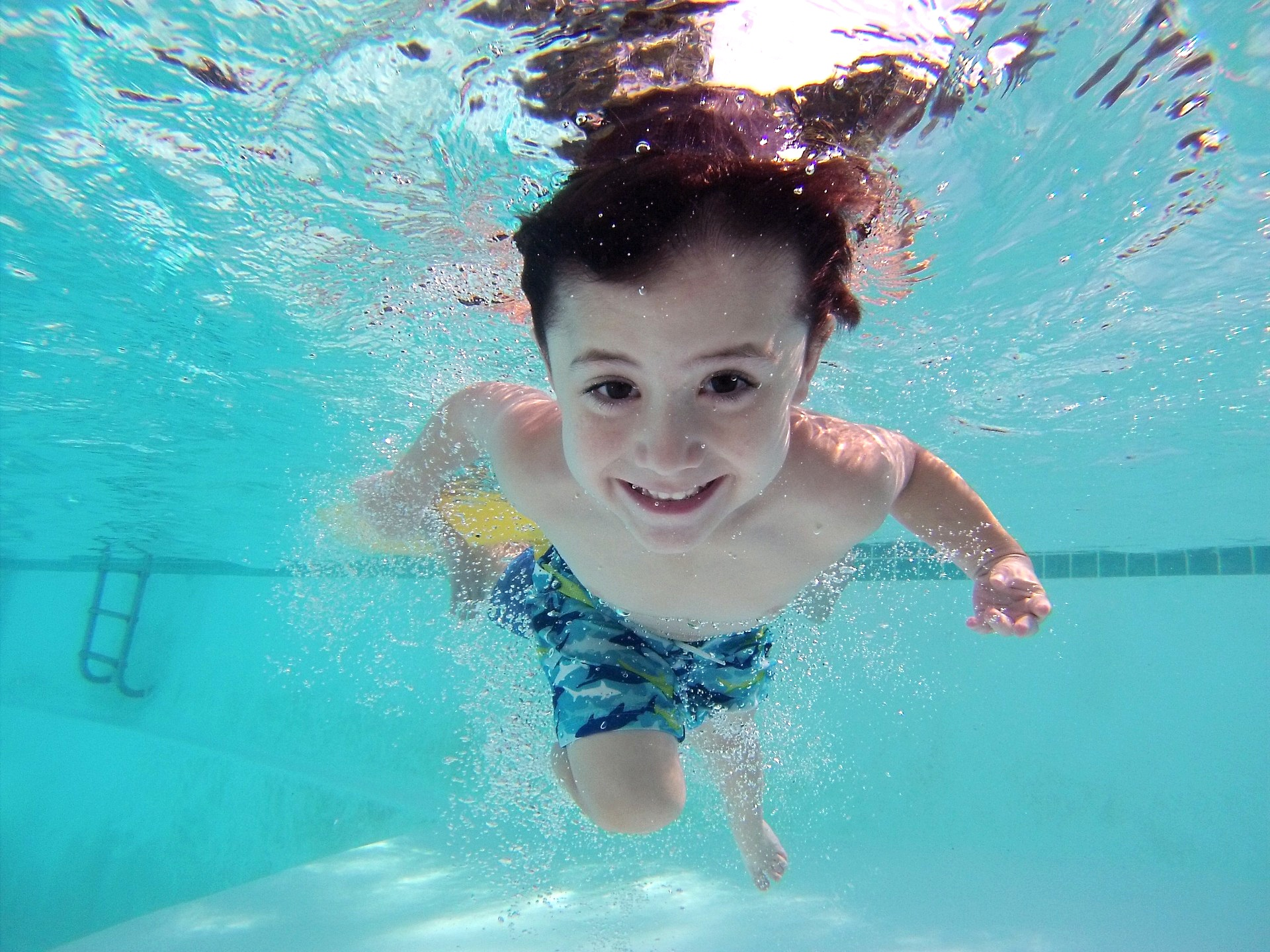 child underwater at swimming pool